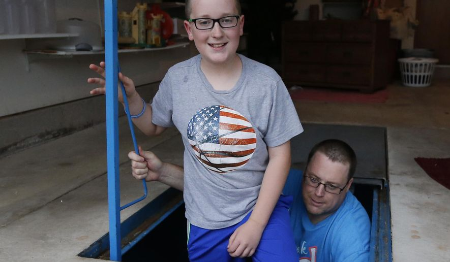 Gabriel Wheeler, left, and David Wheeler, right, pose for a photo in their storm shelter in Oklahoma City, Friday, May 8, 2015. Wheeler has the shelter stocked with blankets and flashlights. (AP Photo/Sue Ogrocki)