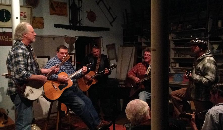 Bill Aeschliman, left, owner of the Chair Place in Craddockville, Va. and other musicians play during a jam session on Thursday, April 23, 2015. The old general store has been a meeting place for Eastern Shore of Virginia residents for more than a century, but that tradition is in peril because of expensive repairs that need to be made, and soon, to keep the building open. Insurers tell Aeschliman it needs a new roof and heating system, both of which come with a hefty price tag.  (Carol Vaughn/The Daily Times via AP)  NO SALES