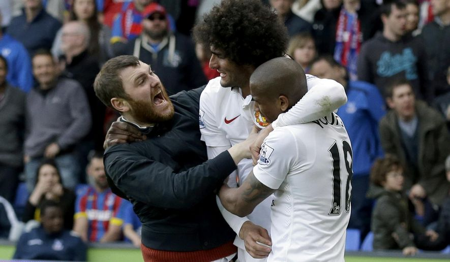 A Manchester United fan, left, joins in celebrations with Marouane Fellaini, second left, after he scored his side's second goal during the English Premier League soccer match between Crystal Palace and Manchester United at Selhurst Park stadium in London, Saturday, May 9, 2015.  (AP Photo/Matt Dunham)