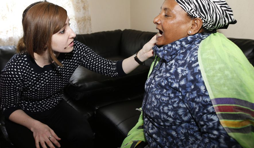 In this photograph taken Monday, April 20, 2015, Marissa Hudak, left, a University of Colorado medical student, checks some recent dental work for Welanza Sahle, a refugee from Ethiopia, in the women's apartment in Aurora, Colo. A program at the medical school sends students out to offer care to refugees struggling to understand the intracacies of the American medical system while trying to integrate into society at the same time. (AP Photo/David Zalubowski)