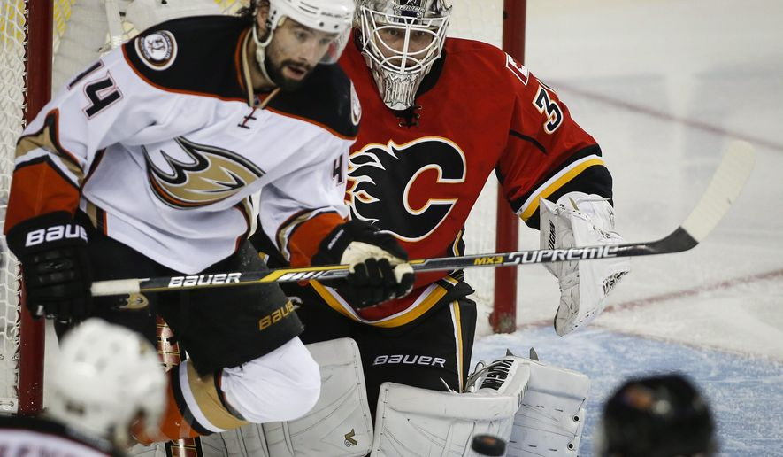 Anaheim Ducks' Nate Thompson, left, looks on as Calgary Flames goalie Karri Ramo, from Finland, stops a shot during the second period of Game 4 of NHL hockey second-round playoff action in Calgary, Alberta, Friday, May 8, 2015. (Jeff McIntosh/The Canadian Press via AP) MANDATORY CREDIT