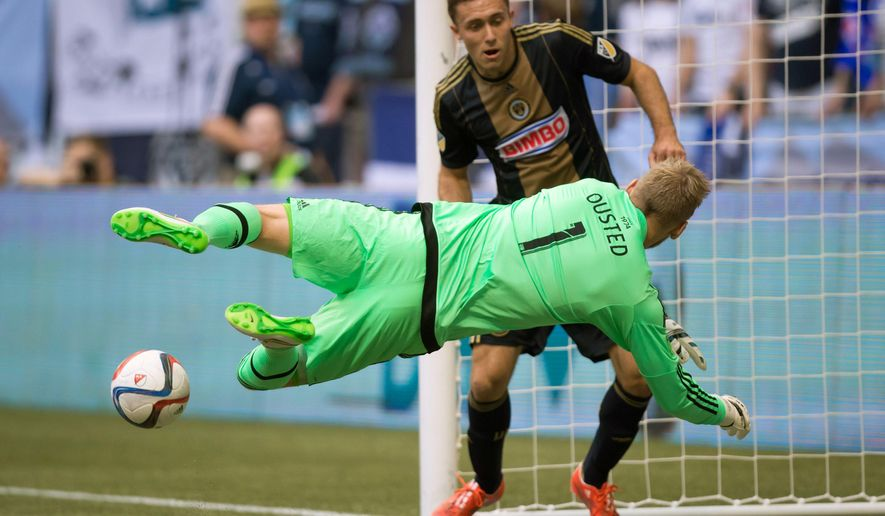 Vancouver Whitecaps goalkeeper David Ousted (1), of Denmark, stops Philadelphia Union's Andrew Wenger during the first half of an MLS soccer game in Vancouver, British Columbia, Saturday May 9, 2015. (Darryl Dyck/The Canadian Press via AP) MANDATORY CREDIT