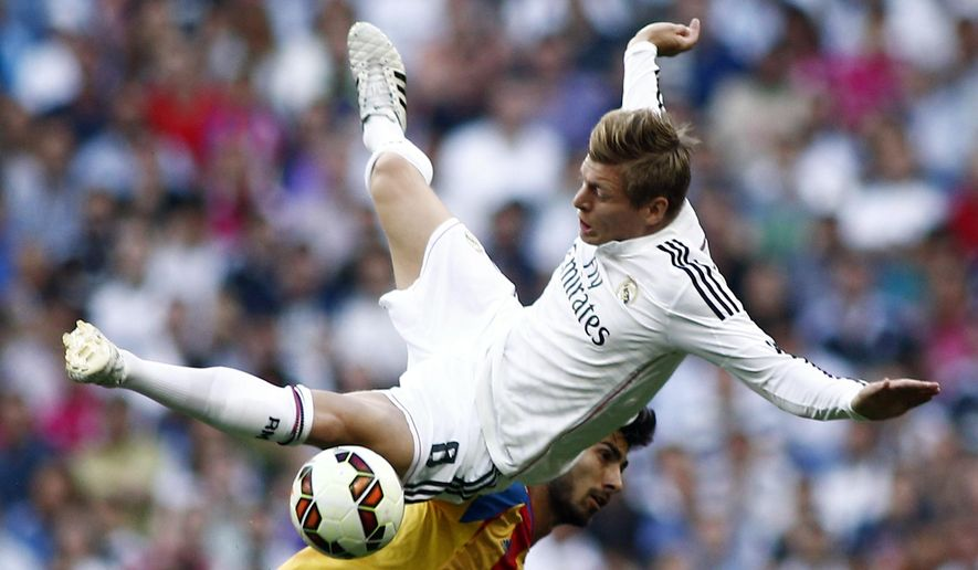 Real Madrid's Toni Kroos, top, duels for the ball with Valencia's Andres Gomes during a Spanish La Liga soccer match at the Santiago Bernabeu stadium in Madrid, Spain, Saturday May 9, 2015. (AP Photo/Oscar del Pozo)