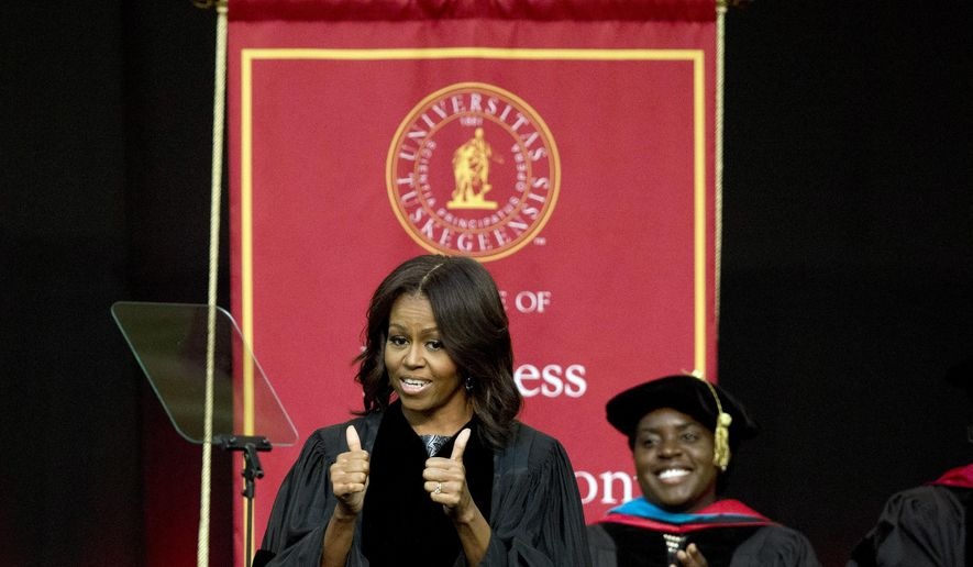 First lady Michelle Obama gives a thumbs up after walking out on stage just before deliveringthe commencement address at Tuskegee University, Saturday, May 9, 2015, in Tuskegee, Ala. (AP Photo/Brynn Anderson)