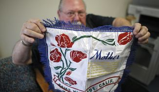 In this photo taken, Tuesday, May 5, 2015, Don Lamoureux displays a World War II era pillow sham at a senior center in Millville, Mass., which his son purchased from an online auction site. Dominic O'Gara had mailed the elaborate pillow sham from his U.S. Army base in California to his mother in Millville in 1942. The Lamoureux's tried to find the soldier's relatives to give it to them, but were unable to find any. The plan now is to put the sham on display in the town's senior center, just yards from the house where the O'Gara family once lived. (AP Photo/Steven Senne)