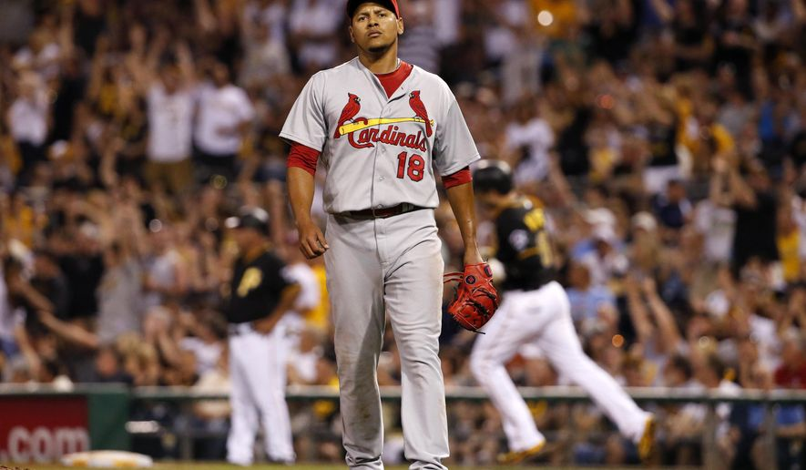 St. Louis Cardinals starting pitcher Carlos Martinez (18) waits as Pittsburgh Pirates' Neil Walker, right rear, rounds first after hitting a solo home run in the fifth inning of a baseball game in Pittsburgh, Saturday, May 9, 2015. (AP Photo/Gene J. Puskar)