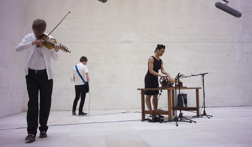 Camille Normant, right, plays the glass armonica during a performance with her trio inside the Nordic Pavilion 'Rapture' at the 2015 Biennale of Arts in Venice, Italy, Wednesday, May 6, 2015. (AP Photo/Domenico Stinellis)