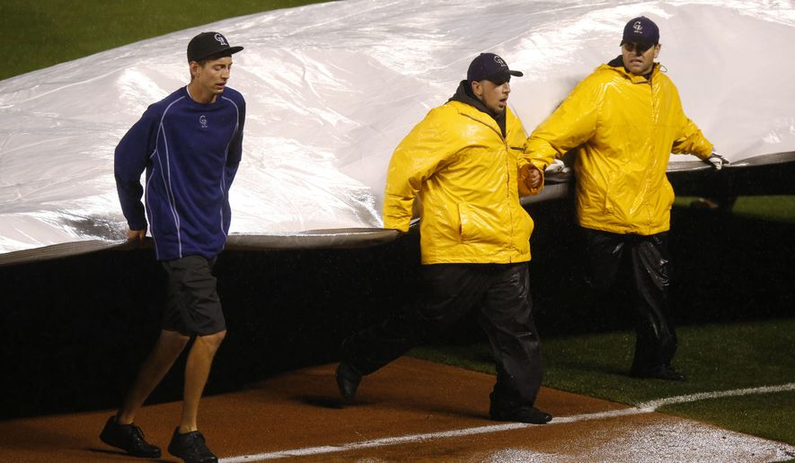 Grounds crew members pull the tarpaulin onto the diamond of Coors Field in the sixth inning of a baseball game between the Los Angeles Dodgers and the Colorado Rockies Friday, May 8, 2015, in Denver. The delay was the second of the game. (AP Photo/David Zalubowski)