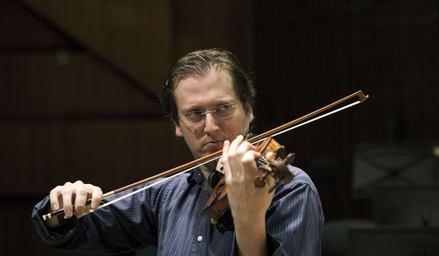 In this Sunday, May 3, 2015 photo, David Radzynski an American-Israeli  concertmaster of the Israel Philharmonic Orchestra, plays during a rehearsal in Tel Aviv concert hall. Radzynski is still getting used to his first job out of college as the new concertmaster of the Israel Philharmonic Orchestra - and to being one of the youngest violinists to lead a major world orchestra today. (AP Photo/Tsafrir Abayov)