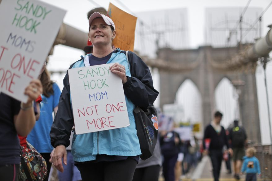 Beth Hegarty, a Sandy Hook Elementary School mother who happened to be inside the school the day of the shooting with her three daughters, all of whom survived, marches over the Brooklyn bridge during the third annual Brooklyn bridge march and rally to end gun violence Saturday, May 9, 2015, in New York. Organizers said the proliferation of guns results in an average of more than 80 deaths a day across the country. (AP Photo/Mary Altaffer)