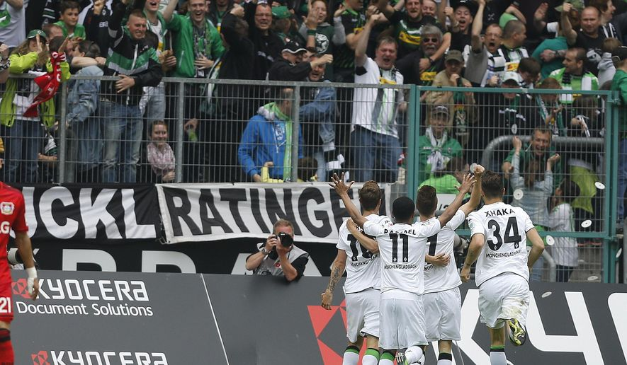 Moenchengladbach teammates celebrate after scoring during the German first division Bundesliga soccer match between Borussia Moenchengladbach and Bayer Leverkusen in Moenchengladbach, Germany, Saturday, May 9, 2015. (AP Photo/Frank Augstein)