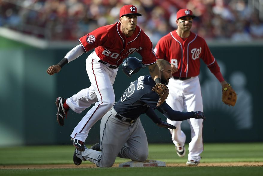 Atlanta Braves' Nick Markakis (22) is safe at second as Washington Nationals shortstop Ian Desmond (20) follows through on his throw to first to get Andrelton Simmons out during the sixth inning of a baseball game, Saturday, May 9, 2015, in Washington. The Nationals won 8-6. Also seen is Washington Nationals second baseman Danny Espinosa (8). (AP Photo/Nick Wass)