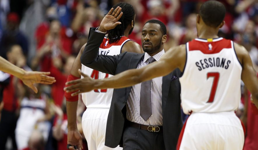 Washington Wizards guard John Wall, in suit, celebrates with guard Ramon Sessions (7) during a break in the first half of Game 3 of the second round of the NBA basketball playoffs against the Atlanta Hawks, Saturday, May 9, 2015, in Washington. Wall is out with a hand injury. (AP Photo/Alex Brandon)