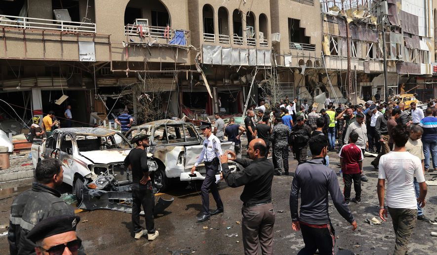 Civilians and security forces inspect the scene of a car bomb explosion in Karrada neighborhood, Baghdad, Iraq, Saturday, May 9, 2015. (Associated Press) ** FILE **