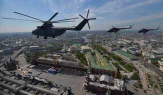 A Russian air force Mi-26 helicopter, front, flies over Red Square during the Victory Parade marking the 70th anniversary of the defeat of the Nazis in World War II, in Red Square in Moscow, Russia, Saturday, May 9, 2015. (Host photo agency/RIA Novosti Pool Photo via AP) ** FILE **