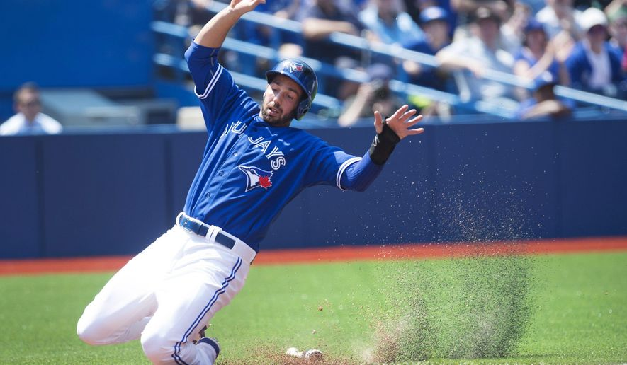 Toronto Blue Jays' Chris Colabello slides safely into home plate to score on a Josh Donaldson RBI single during second inning baseball action against the Boston Red Sox in Toronto on Saturday, May 9, 2015. (Darren Calabrese/The Canadian Press via AP)
