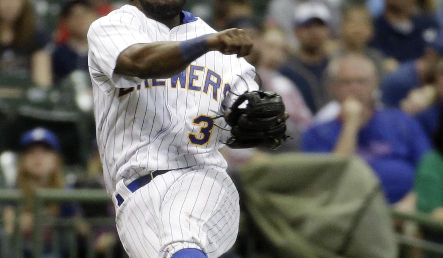 Milwaukee Brewers' Elian Herrera makes a wild throw on a ball hit by Chicago Cubs' Addison Russell during the ninth inning of a baseball game Friday, May 8, 2015, in Milwaukee. The throw was ruled an error. (AP Photo/Morry Gash)