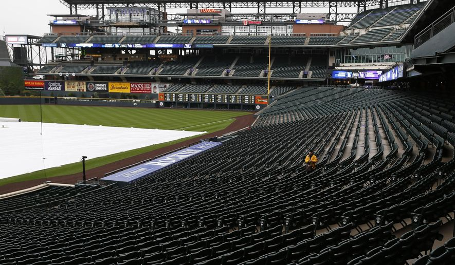 A lone guard moves through the empty stands in Coors Field after the cancellation of a baseball game between the Los Angeles Dodgers and the Colorado Rockies, Saturday, May 9, 2015, in Denver. Forecasters are predicting three to five inches of snow to fall in the Denver metropolitan area overnight as a spring storm sweeps over the intermountain West. (AP Photo/David Zalubowski)