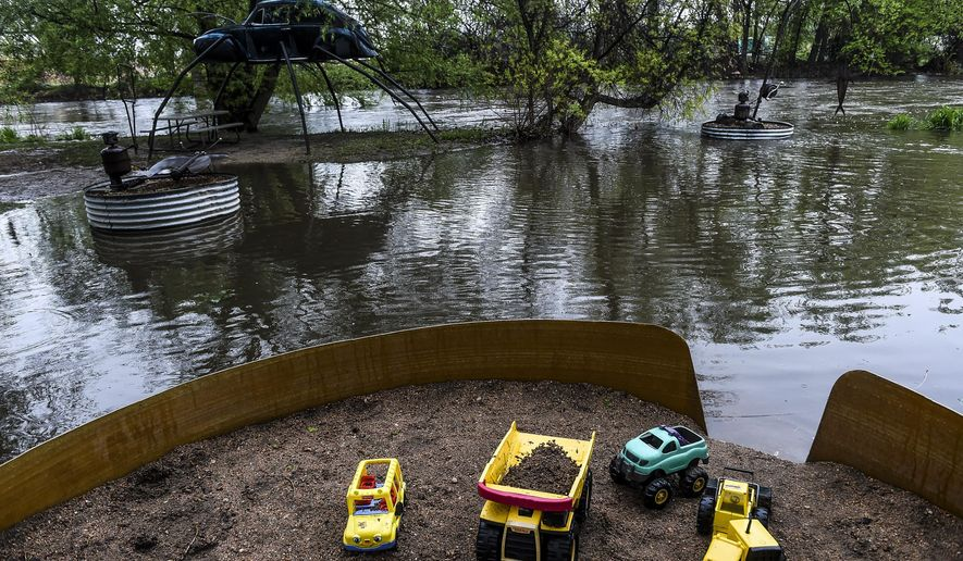 Figures in the Swetsville Zoo in Fort Collins, Colo. are surrounded by water as levels along the Poudre River are high with more rain expected in the Fort Collins and Windsor area, Friday, May 8, 2015. (Erin Hall/The Coloradoan via AP) MANDATORY CREDIT