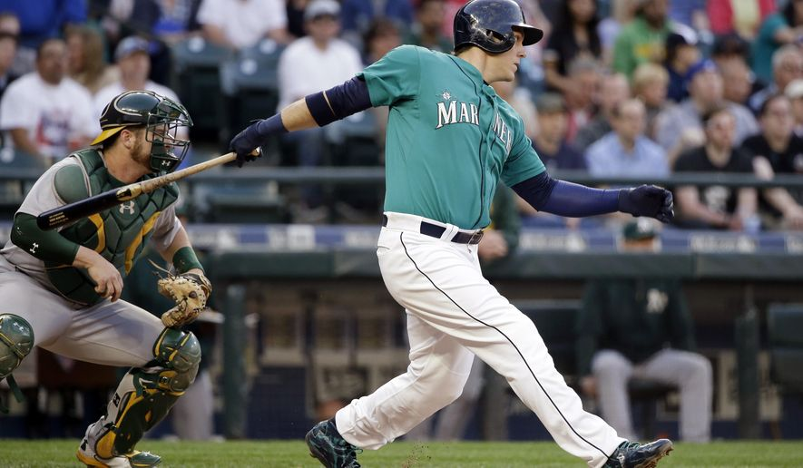 Seattle Mariners' Logan Morrison singles in a run against the Oakland Athletics in the second inning of a baseball game Friday, May 8, 2015, in Seattle. (AP Photo/Elaine Thompson)