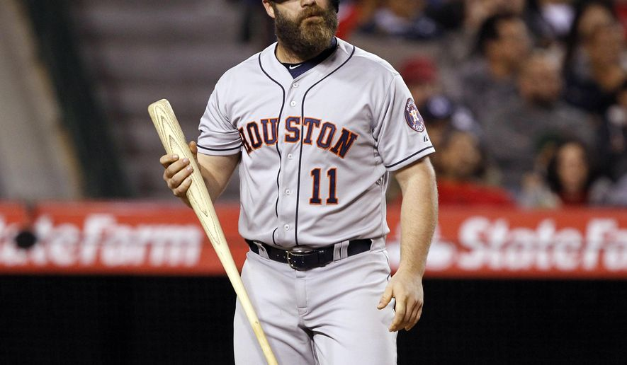 Houston Astros designated hitter Evan Gattis (11) walks back to the bench after striking out against the Los Angeles Angels during the ninth inning of a baseball game in Anaheim, Calif., Friday, May 8, 2015. The Angels won the game 2-0. (AP Photo/Alex Gallardo)