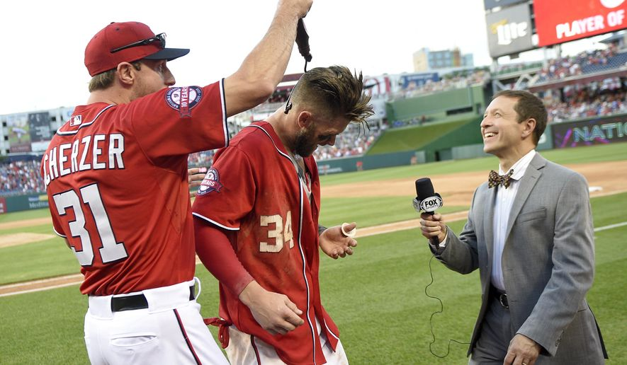 Washington Nationals' Bryce Harper, center, has chocolate sauce poured on him by teammate Max Scherzer, left, after Harper hit a two-run walk-off home run in the ninth inning of a baseball game against the Atlanta Braves to end the game, Saturday, May 9, 2015, in Washington. The Nationals won 8-6. (AP Photo/Nick Wass)