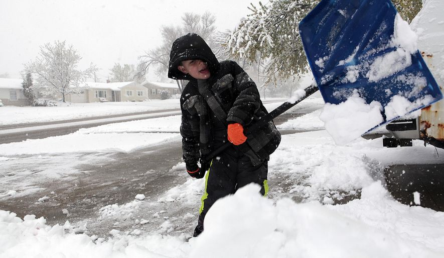 Josyah Puckett, 6, helps clear off his driveway on Fairmont Boulevard Sunday morning in Rapid City, S.D. after the Black Hills were hit with a large snowstorm.  Some parts of Rapid City saw 10 inches of snow by Sunday morning with more forecast throughout the day. (Chris Huber/Rapid City Journal via AP) TV OUT