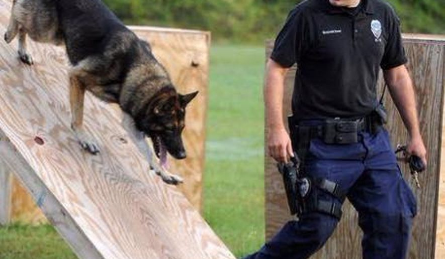 In this undated photo released by the Hattiesburg Police Department, Officer Benjamin Deen participates in K-9 training at the police academy in Hattiesburg, Miss. Officer Deen and Officer Liquori Tate were fatally shot during a traffic stop, Saturday evening, May 9, 2015, in the southern Mississippi city of Hattiesburg, prompting a statewide manhunt early Sunday for two suspects, authorities said. (Hattiesburg Police Department via AP)