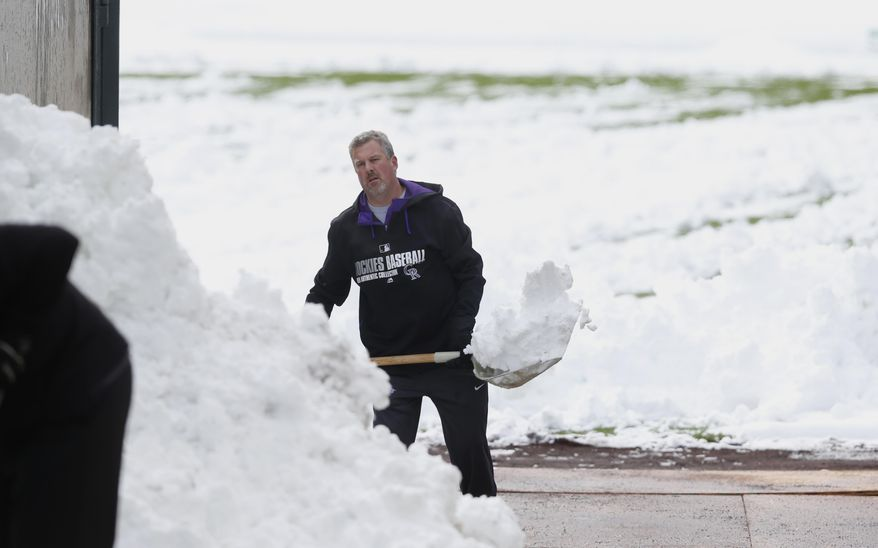 Alan Bossart, visiting clubhouse manager for the Colorado Rockies, shovels snow off the outfield in Coors Field after a wet, heavy snow Sunday, May 10, 2015, in Denver. Groundskeepers are hurrying to prepare the field for the baseball game scheduled for Sunday between the Los Angeles Dodgers and the Rockies. The spring storm that left the snow in Denver has wreaked havoc across the state, triggering flood warnings in northeast counties while dropping up to 18 inches of snow in the southern parts of the Centennial State. (AP Photo/David Zalubowski)