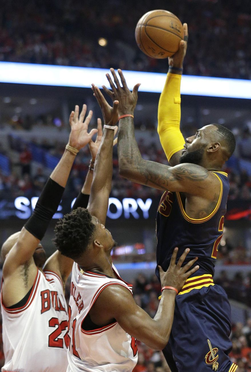 Cleveland Cavaliers forward LeBron James, right, shoots over Chicago Bulls forward Taj Gibson, left, and guard Jimmy Butler during the first half of Game 4 in a second-round NBA basketball playoff series in Chicago on Sunday, May 10, 2015. (AP Photo/Nam Y. Huh)