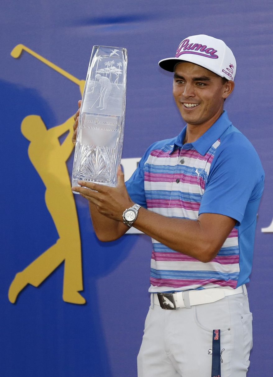 Rickie Fowler holds The Players Championship trophy Sunday, May 10, 2015, in Ponte Vedra Beach, Fla. Fowler won in a sudden death playoff against Kevin Kisner. (AP Photo/John Raoux)