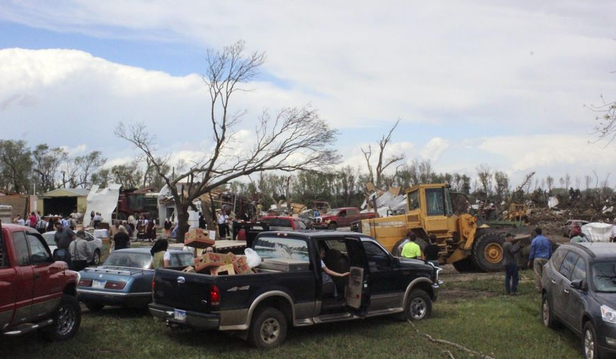 Dozens of people gather to help with cleanup efforts at a farm that was severely damaged by a tornado Sunday, May 10, 2015, in Delmont, S.D. South Dakota was the center of weather extremes Sunday, with a tornado hitting the small town on the eastern side of the state and more than a foot of snow blanketing the Black Hills to the west. (AP Photo/Regina Garcia Cano)