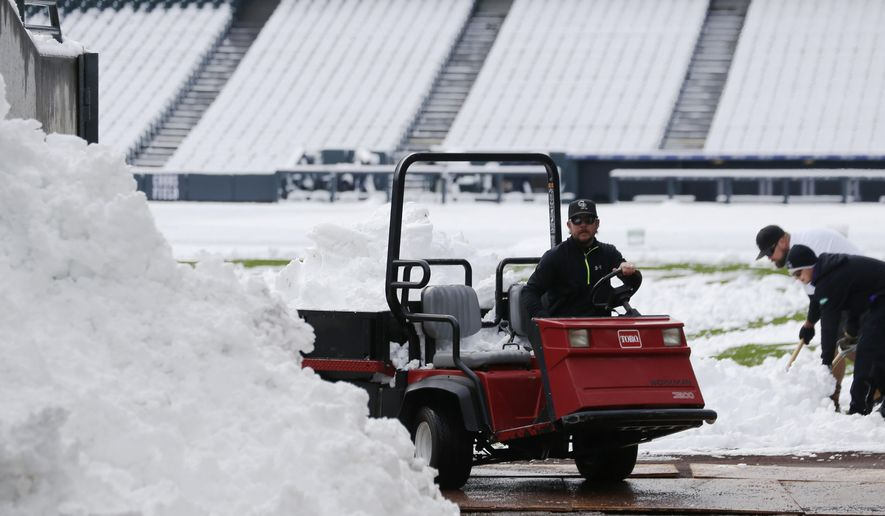 Grounds crew members at Coors Field work to clear the outfield of a wet, heavy snow Sunday, May 10, 2015, in Denver. Workers are hurrying to prepare the field for Sunday's baseball game when the Colorado Rockies host the Los Angeles Dodgers. The spring storm wreaked havoc across the state, triggering flood warnings in northeast counties while dropping up to 18 inches of snow in the southern parts of the Centennial State. (AP Photo/David Zalubowski)