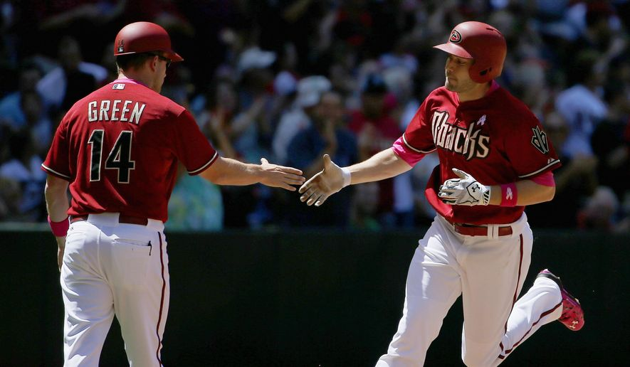 Arizona Diamondbacks' A.J. Pollock, right, shakes hands with third base coach Andy Green (14) as he rounds the bases after hitting a home run against the San Diego Padres during the third inning of a baseball game Sunday, May 10, 2015, in Phoenix. (AP Photo/Ross D. Franklin)