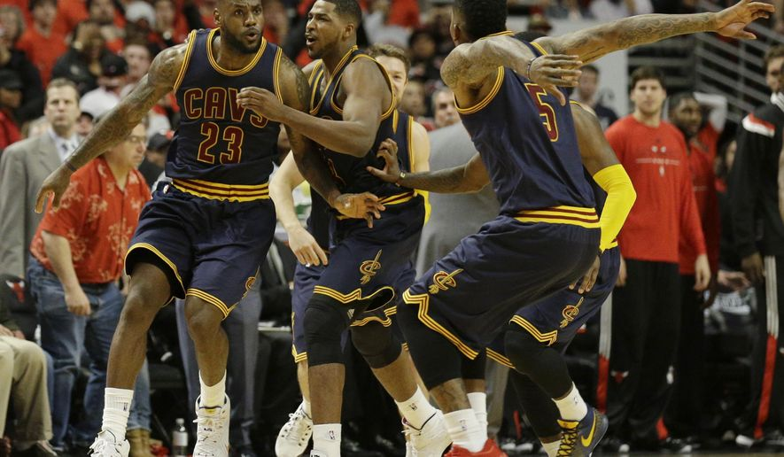 Cleveland Cavaliers' LeBron James, left, celebrates with Tristan Thompson, center and J.R. Smith after scoring the game-winning basket during the second half of Game 4 in a second-round NBA basketball playoff series against the Chicago Bulls in Chicago on Sunday, May 10, 2015. The Cavaliers won 86-84. (AP Photo/Nam Y. Huh)