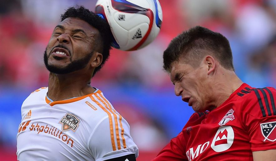 Houston Dynamo Giles Barnes, left, battles for the ball with Toronto FC Nick Hagglund, during first half MLS soccer action in Toronto on Sunday, May 10, 2015. (Frank Gunn/The Canadian Press via AP)