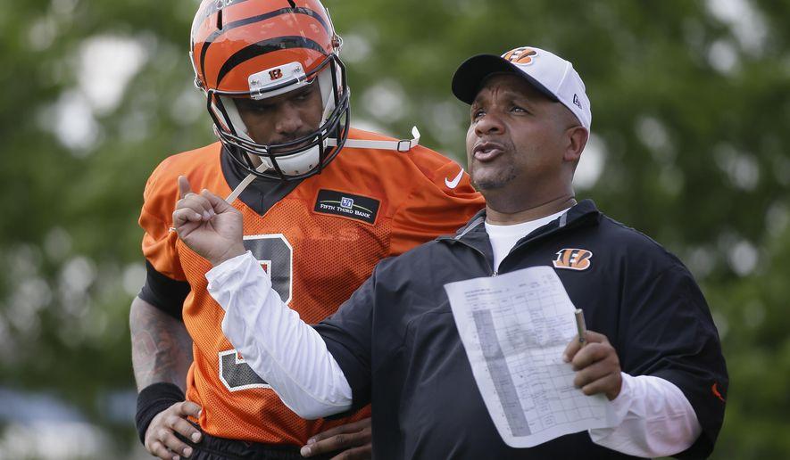 Cincinnati Bengals rookie quarterback Terrelle Pryor is coached by offensive coordinator Hue Jackson during an NFL football rookie minicamp Friday, May 8, 2015, in Cincinnati. (AP Photo/John Minchillo)