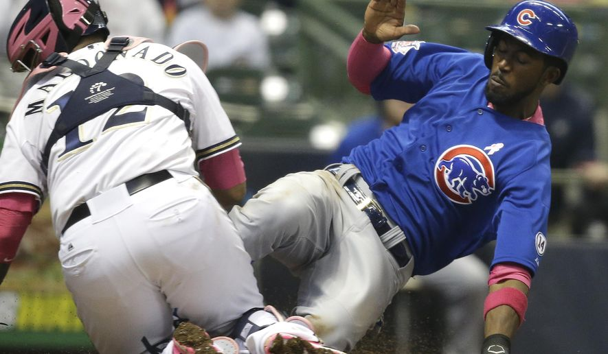Chicago Cubs' Dexter Fowler, right, scores as the ball gets away from Milwaukee Brewers catcher Martin Maldonado during the eighth inning of a baseball game Sunday, May 10, 2015, in Milwaukee. (AP Photo/Jeffrey Phelps)