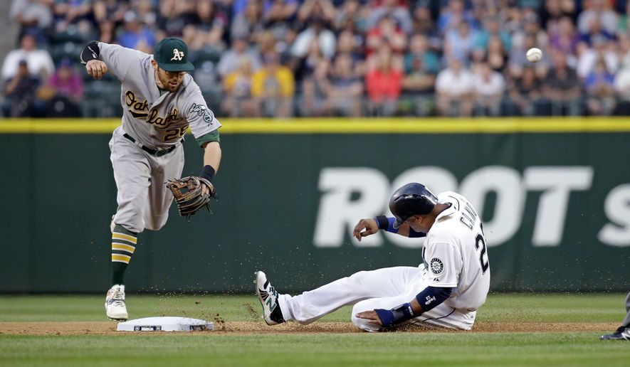 Seattle Mariners' Robinson Cano, right, slides safely into second base as Oakland Athletics second baseman Eric Sogard misses the throw to him on a throwing error by third baseman Brett Lawrie during the fifth inning of a baseball game Saturday, May 9, 2015, in Seattle. (AP Photo/Elaine Thompson)