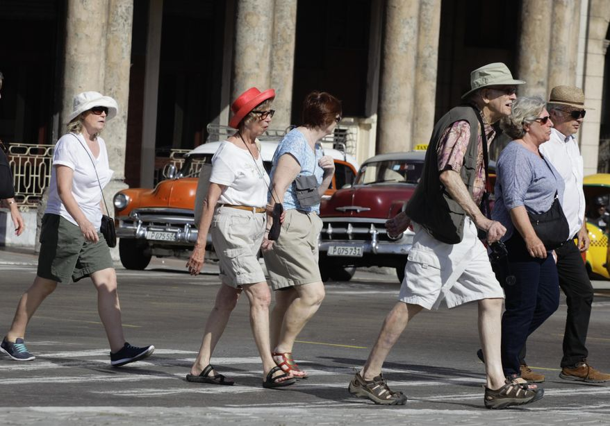 FILE - In this March 13, 2015 file photo, tourists cross traffic lights in Havana, Cuba. Tourists in shorts and sandals aren't the only foreigners flooding Havana these days. Top diplomats from Japan, the European Union, Italy, the Netherlands and Russia have visited the island in recent months in a bid to stake out or maintain ties with an island that suddenly looks like a brighter economic prospect amid warming U.S.-Cuba relations. (AP Photo/Desmond Boylan, File)
