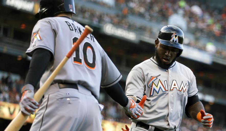 Miami Marlins' Marcell Ozuna, right, is congratulated by teammate Jeff Baker (10) after hitting a home run off San Francisco Giants' Madison Bumgarner in the fourth inning of a baseball game Saturday, May 9, 2015, in San Francisco. (AP Photo/Ben Margot)
