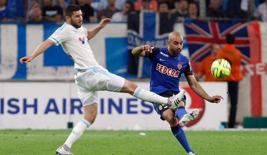 Marseille's Andre-Pierre Gignac, left,  challenges for the ball with Monaco's Aymen Abdennour , during the League One soccer match between Marseille and Monaco, at the Velodrome Stadium, in Marseille, southern France, Sunday, May 10, 2015. (AP Photo/Claude Paris)