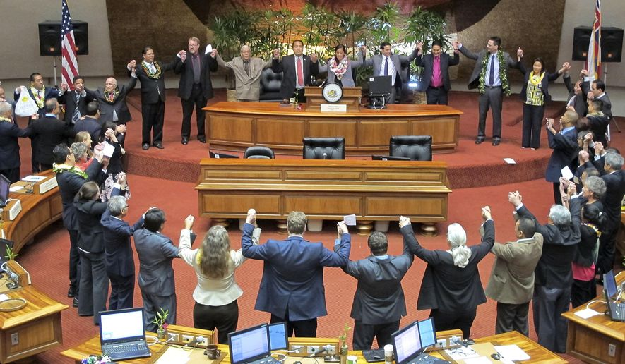 "In this May 7, 2015 photo, Hawaii lawmakers hold hands and sing ""Hawaii Aloha"" as they celebrate passing the final bills of the 2015 session in Honolulu. (AP Photo/Cathy Bussewitz)"