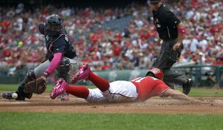 Washington Nationals' Ryan Zimmerman, front right, slides home to score against Atlanta Braves catcher Christian Bethancourt, left, during the first inning of a baseball game, Sunday, May 10, 2015, in Washington. Zimmerman scored on a hit by Wilson Ramos. (AP Photo/Nick Wass)