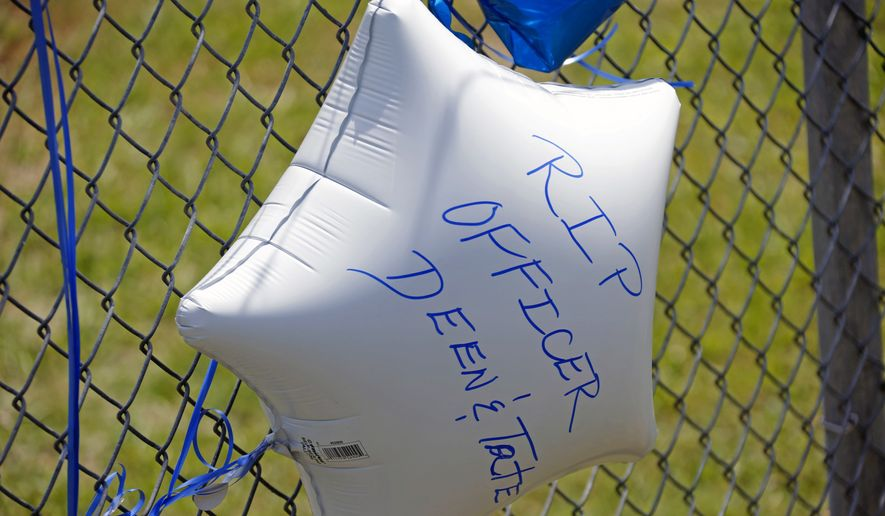 A memorial balloon with a personal message floats at a makeshift memorial in Hattiesburg, Miss., Sunday, May 10, 2015. Two officers were shot to death during an evening traffic stop turned violent, a state law enforcement spokesman said Sunday. Three suspects were in custody, including two who are charged with capital murder. (AP Photo/Rogelio V. Solis)