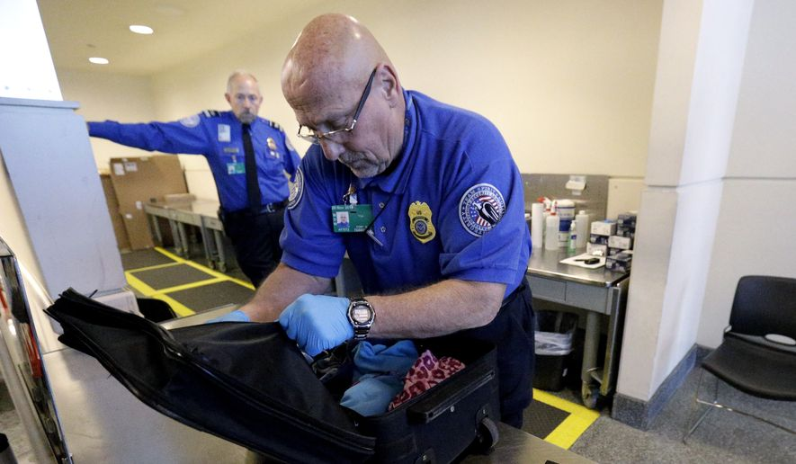 A TSA agent checks a bag at a security checkpoint area at Midway International Airport in Chicago. Two TSA managers say they were punished after exposing major security problems at the Minneapolis-St. Paul International Airport. (Associated Press)