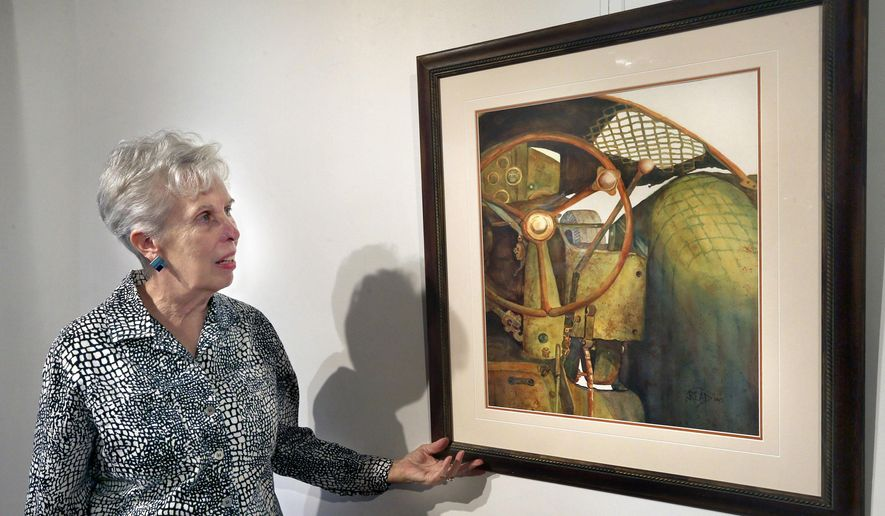 "FOR RELEASE SUNDAY, MAY 10, 2015, AT 9:00 A.M. EDT.-Artist Julie Read stands with one of her watercolor paintings titled, ""Retired or Just Tired"" Thursday, May 6, 2015.  Her work will be featured in the upcoming Shenandoah Arts Council show, Fifty Shades of Rust in Winchester, Virginia. (Scott Mason/The Winchester Star via AP)"