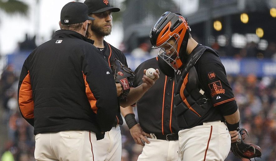 San Francisco Giants pitching coach Dave Righetti, left, meets with Madison Bumgarner and catcher Buster Posey, right, in the fourth inning of a baseball game against the Miami Marlins, Saturday, May 9, 2015, in San Francisco. (AP Photo/Ben Margot)