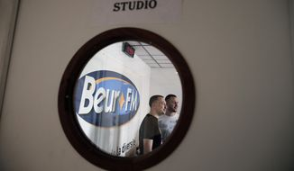 """In this  Friday, April 17, 2015 photo men work at Beur FM radio in Paris. It's called """"Beur FM"""" - after a slang term for Arab people - and has become the voice of France's Islamic community in the wake of the Charlie Hebdo attacks. Since terror struck the heart of Paris in January, Beur FM has become a staple for listeners of all walks of life who are hungry for answers about the violence - and how to reconcile alienated immigrants with mainstream society. (AP Photo/Christophe Ena)"""