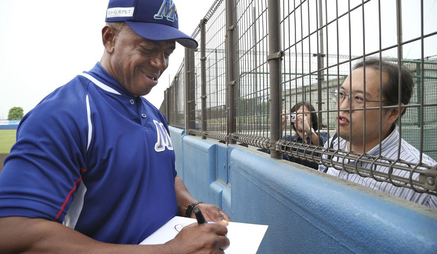 In this Saturday, May 9, 2015 photo, former Major League Baseball player and manager of Ishikawa Million Stars Julio Franco, 56,  gives his autographs to Japanese fans before a game at a stadium in Konosu, north of Tokyo.  When Franco signed a contract with the Million Stars, Franco saw himself more as a manager than player but that hasn't been the case so far. Due to an injury to a key player, Franco finds himself playing more than he expected.  (AP Photo/Koji Sasahara)